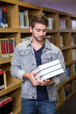 Studente che sorride alla macchina fotografica in biblioteca Fotografie Stock