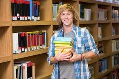 Studente che sorride alla macchina fotografica in biblioteca Immagine Stock Libera da Diritti