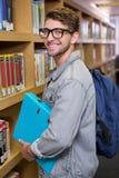 Studente che sorride alla macchina fotografica in biblioteca Fotografia Stock Libera da Diritti