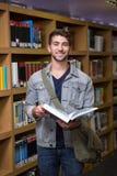 Studente che sorride alla macchina fotografica in biblioteca Immagine Stock