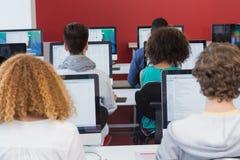 Studente che sorride alla macchina fotografica nella classe del computer Fotografie Stock Libere da Diritti
