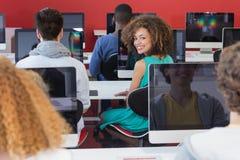 Studente che sorride alla macchina fotografica nella classe del computer Immagini Stock