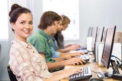Studente che sorride alla macchina fotografica nella classe del computer Immagine Stock