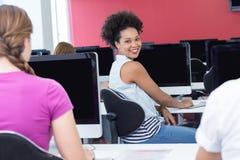 Studente che sorride alla macchina fotografica nella classe del computer Fotografie Stock