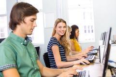 Studente che sorride alla macchina fotografica nella classe del computer Immagini Stock Libere da Diritti