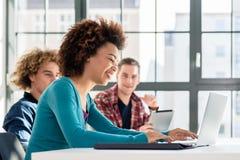 Studente che sorride mentre per mezzo di un computer portatile per le informazioni online Fotografia Stock