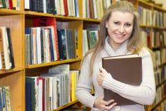 Studente che sta allo scaffale per libri in vecchia biblioteca Fotografia Stock Libera da Diritti