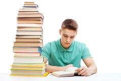 Studente che studia ad una tavola con una pila di libri Immagini Stock Libere da Diritti