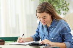 Studente che studia calcolazione con un calcolatore Fotografie Stock Libere da Diritti