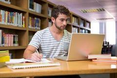 Studente che studia nella biblioteca con il computer portatile Fotografia Stock