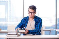 Studente che studia nella biblioteca vuota con il libro che prepara per ex Fotografia Stock