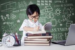 Studente che studia nella classe con l'orologio ed il computer portatile Fotografia Stock