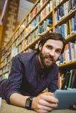 Studente che studia sul pavimento in biblioteca che indossa orologio astuto Immagini Stock Libere da Diritti