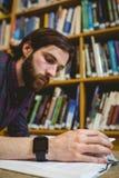 Studente che studia sul pavimento in biblioteca che indossa orologio astuto Fotografia Stock