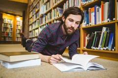 Studente che studia sul pavimento nella biblioteca Fotografia Stock Libera da Diritti