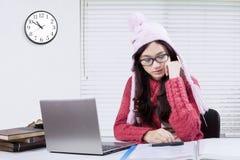 Studente che studia sullo scrittorio con un orologio sulla parete Fotografia Stock Libera da Diritti