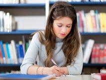 Studente che studia in una biblioteca Fotografie Stock Libere da Diritti