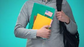 Studente che tiene i taccuini con la bandiera di U.S.A., programma educativo internazionale video d archivio