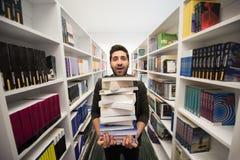 Studente che tiene lotto dei libri nella biblioteca di scuola Immagini Stock Libere da Diritti