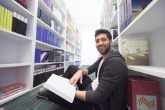 Studente che tiene lotto dei libri nella biblioteca di scuola Fotografia Stock Libera da Diritti