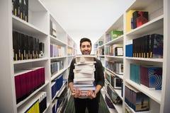 Studente che tiene lotto dei libri nella biblioteca di scuola Fotografia Stock