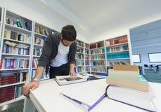 Studente che tiene lotto dei libri nella biblioteca di scuola Immagini Stock
