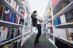 Studente che tiene lotto dei libri nella biblioteca di scuola Immagine Stock Libera da Diritti