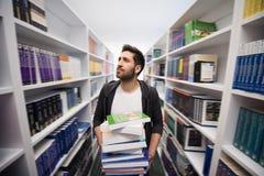 Studente che tiene lotto dei libri nella biblioteca di scuola Immagine Stock