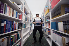 Studente che tiene lotto dei libri nella biblioteca di scuola Fotografie Stock