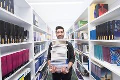 Studente che tiene lotto dei libri nella biblioteca di scuola Fotografie Stock Libere da Diritti