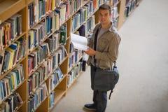 Studente che tiene un libro dallo scaffale in biblioteca che sorride alla macchina fotografica Fotografie Stock Libere da Diritti