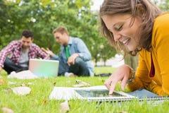 Studente che utilizza il PC della compressa mentre maschi facendo uso del computer portatile nel parco Fotografie Stock
