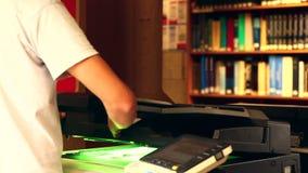 Studente che utilizza la fotocopiatrice nella biblioteca stock footage