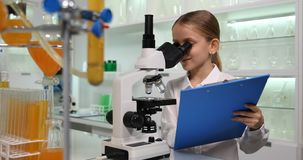 Studente Child Use Microscope, funzionamento della ragazza per istruire progetto nel laboratorio di chimica 4K stock footage