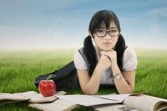 Studente cinese sveglio che si trova sull'erba Immagine Stock