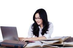 Studente con capelli lunghi che studia allo scrittorio Fotografia Stock