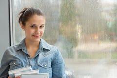 Studente con i libri davanti alla finestra immagine stock