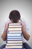 Studente con i lotti dei libri su bianco Fotografia Stock