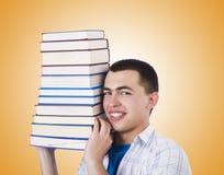 Studente con i lotti dei libri su bianco Immagini Stock