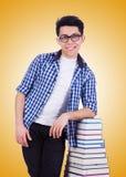 Studente con i lotti dei libri su bianco Fotografie Stock Libere da Diritti