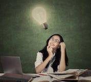 Studente con i manuali che cerca lampada Immagine Stock