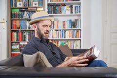 Studente con il cappello che legge un libro davanti ad uno scaffale di libro Fotografia Stock Libera da Diritti