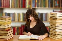 Studente con il libro aperto che lo legge nella biblioteca di istituto universitario Immagini Stock Libere da Diritti