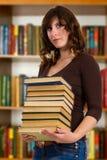 Studente con il libro che lo legge nella biblioteca di istituto universitario Fotografie Stock Libere da Diritti
