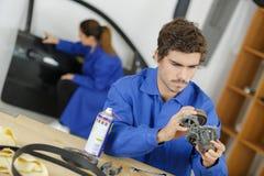 Studente con il ricambio auto che studia commercio automobilistico immagini stock