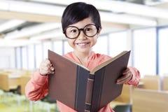 Studente con l'abbigliamento casual che tiene libro nella classe Fotografie Stock