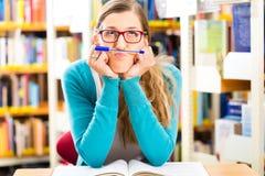 Studente con l'apprendimento di libri nella biblioteca Fotografia Stock
