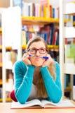 Studente con l'apprendimento di libri nella biblioteca Fotografie Stock Libere da Diritti