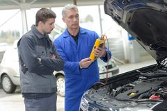 Studente con l'istruttore che ripara automobile durante l'apprendistato immagine stock
