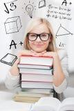 Studente con la pila di libri e di scarabocchi Fotografia Stock